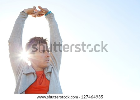 Close up portrait of a sports man stretching his arms up in the air against a sunny blue sky with sun rays filtering through his arm. - stock photo