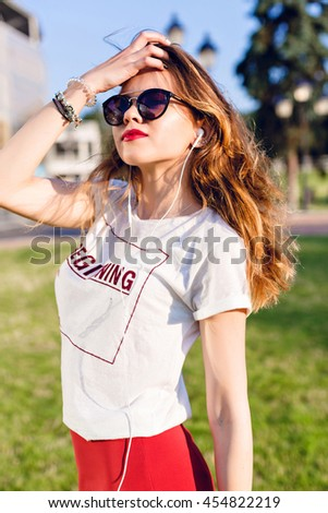 Close-up portrait of a standing young girl listening to music on earphones. Girl wears a white t-shirt, red skirt and dark sunglasses. Girl plays with her hair and has red lipstick on. - stock photo