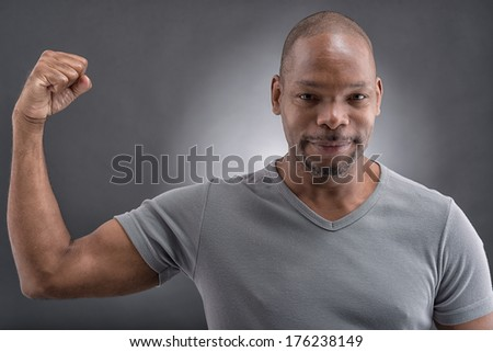 Close-up portrait of a strong young guy showing his muscular over a grey background  - stock photo