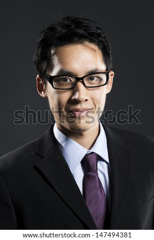 Close up Portrait of a stylish Asian business man standing in front of a dark grey background