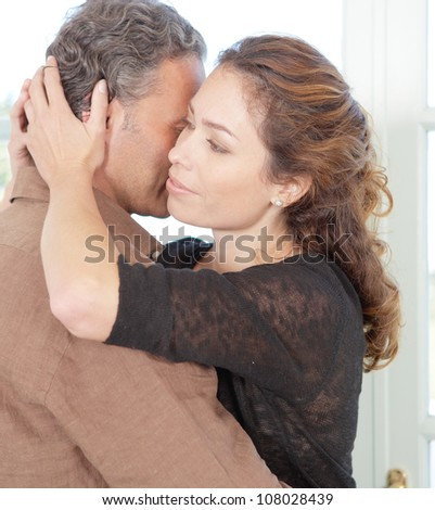 Close up portrait of a stylish mature couple hugging at home. - stock photo