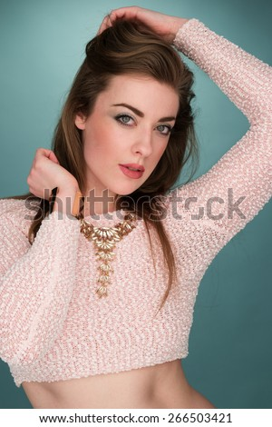 Close up Portrait of a Stylish Pretty Young Woman Posing in Sexy Shirt Showing her Abs with Elegant Gold Necklace While Looking at the Camera. Captured in Studio with Gray Green Gradient Background. - stock photo