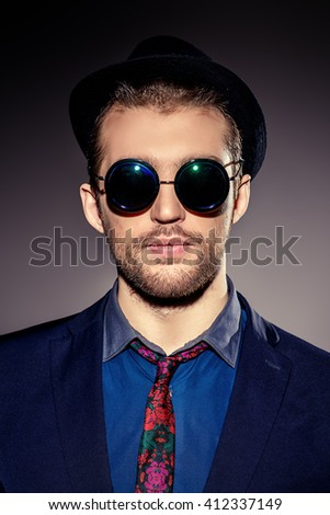 Close-up portrait of a stylish young man wearing black round sunglasses. Optics style. Fashion studio shot. - stock photo