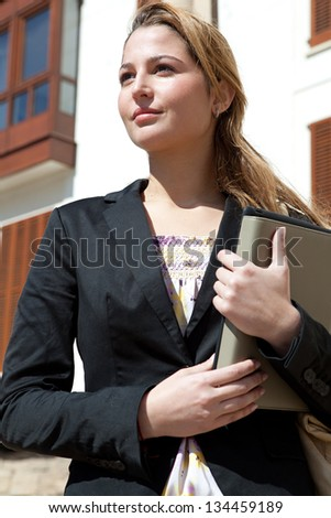 Close up portrait of a successful businesswoman holding a digital tablet pad and a folder while proudly standing near a classic city office buildings.