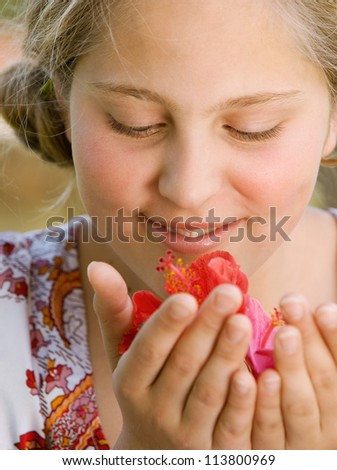 Close up portrait of a teenage girl smelling hibiscus flowers and smiling. - stock photo