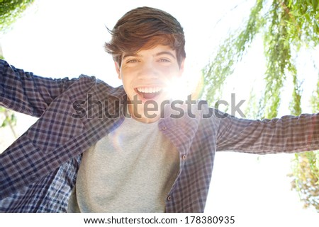 Close up portrait of a teenager boy joyfully smiling expressing happiness and joy while standing against a sunny sky with the sun rays filtering through with flare. Outdoors lifestyle. - stock photo