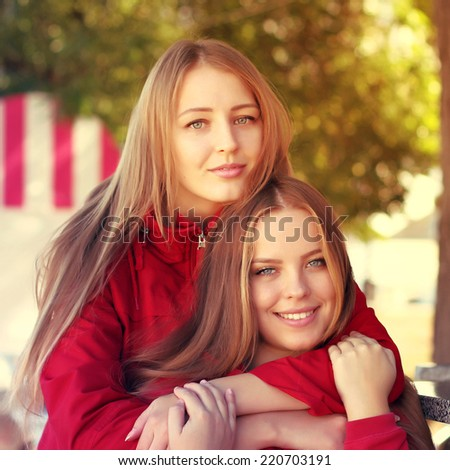 Close up portrait of a teenager daughter and her mother hugging and smiling. Outdoors lifestyle. Photo toned style Instagram filters. - stock photo