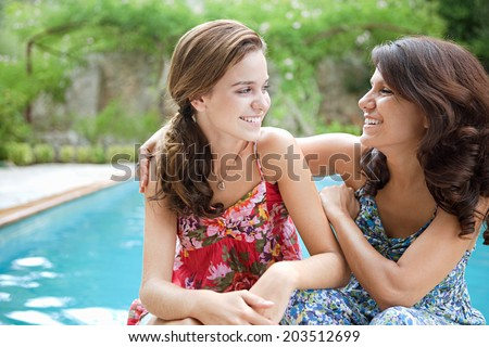 Close up portrait of a teenager daughter and her mother together, joyfully smiling during a summer holiday break in a vacation villa green garden and swimming pool, relaxing outdoors lifestyle. - stock photo