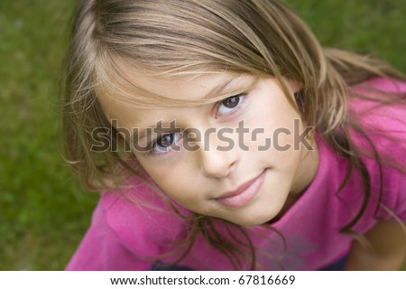 Close up portrait of a ten year old girl, smiling up at the camera. Positive emotion - stock photo