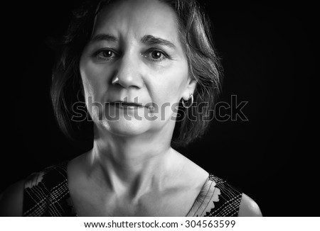 Close-up portrait of a thoughtful woman, middle aged, looking at the camera, isolated on black. Black & white picture. - stock photo
