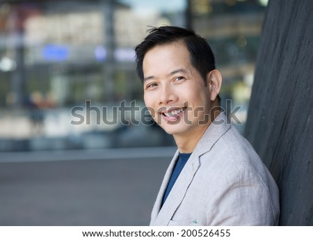 Close up portrait of a trendy asian man smiling outdoors - stock photo