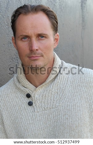 Close up portrait of a trendy young man posing with beige wool sweater