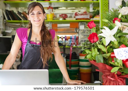 Close up portrait of a welcoming florist business woman owner proudly standing at her flower shop counter using a laptop computer and smiling. Small business technology. - stock photo