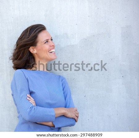 Close up portrait of a woman laughing and looking away - stock photo