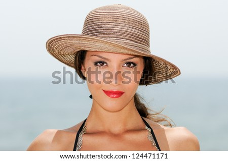 Close up portrait of a woman with a sun hat on a tropical beach - stock photo
