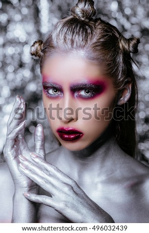 Close-up portrait of a woman with creative make-up on a silver background. Top model covered with silver posing.