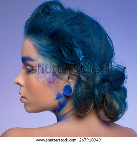 Close-up portrait of a woman with creative make-up on blue background - stock photo