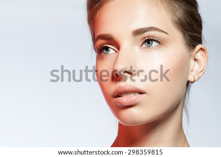 Close-up portrait of a woman with perfect skin clean in the light of the red light - stock photo