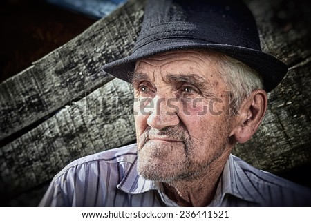 Close-up portrait of a wrinkled and expressive old farmer. - stock photo