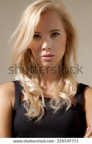 Close up portrait of a young adult attractive sexy and sensuality pretty blonde student woman with beautiful hairs in black dress isolated on grey background