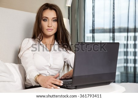 Close up portrait of a young adult beauty attractive sexy and sensuality happy pretty brunette businesswoman using laptop sitting on bed in hotel room - stock photo