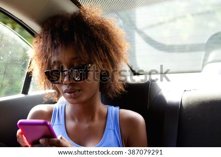 Close up portrait of a young african american woman sitting n backseat of car looking at cell phone  - stock photo