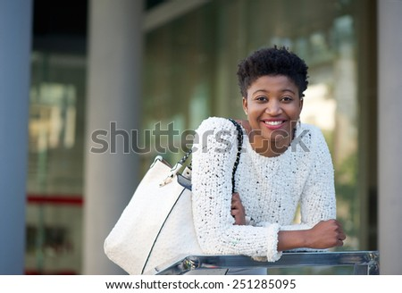 Close up portrait of a young african american woman smiling in the city - stock photo