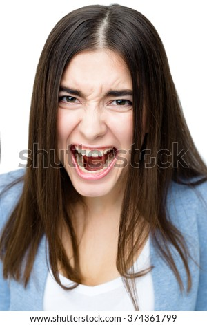Close up portrait of a young and angry woman on white background