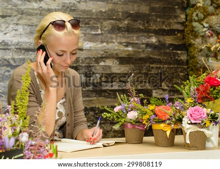 Close up portrait of a young and attractive florist business woman and shop attendant using a smartphone to take an oder over the phone. Working business outdoors. Focus on the model of the left - stock photo