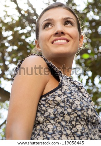 Close up portrait of a young  attractive businesswoman against the leaves of a tree and the sunshine. - stock photo