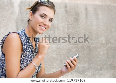 Close up portrait of a young attractive businesswoman using digital technology against a stone wall, outdoors.