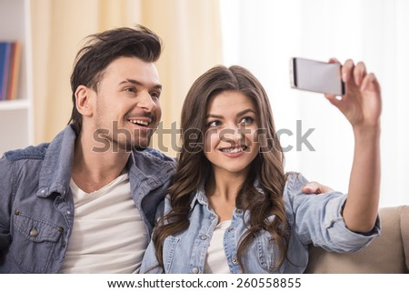 Close-up portrait of a young attractive couple are making a selfie picture at home. - stock photo