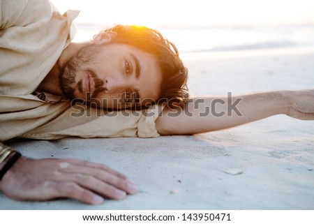 Close up portrait of a young attractive man lying down and relaxing on a white sand beach with the sunset behind him with flare and warm flooding light, on vacation. - stock photo