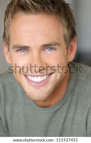 Close-up portrait of a young attractive man with great toothy smile - stock photo