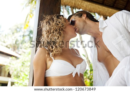 Close up portrait of a young attractive sexy couple kissing while lounging on a garden bed on vacations in a tropical hotel spa destination. - stock photo