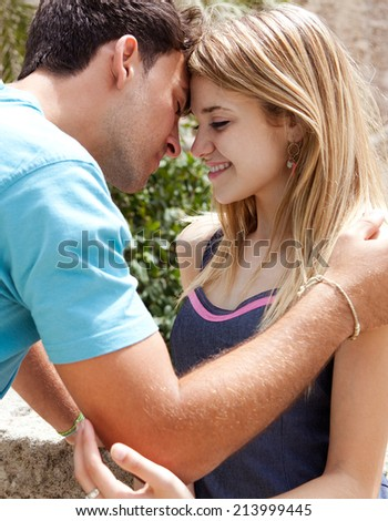 Close up portrait of a young attractive tourist couple being close and in love, holding their heads together in romance while on holiday, visiting a touristic destination city, outdoors. - stock photo