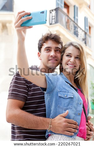 Close up portrait of a young attractive tourist couple on holiday visiting a destination city and sightseeing taking pictures and selfies using a smartphone device. Travel technology outdoors. - stock photo