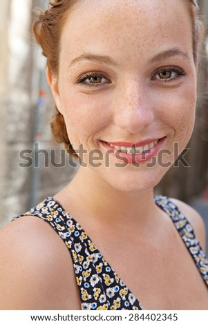 Close up portrait of a young attractive tourist woman visiting a destination city on a summer holiday, looking at camera, joyfully smiling, outdoors. Beauty and well being and skin care, exterior. - stock photo