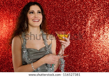 Close up portrait of a young attractive woman holding a cocktail glass while smiling against a red glitter background in a christmas party.