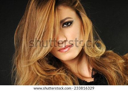 close up portrait of a Young beautiful girl with long blond perfect hair covering half of her face - stock photo