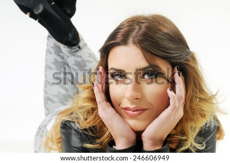 close up portrait of a Young beautiful serious caucasian lady lying down on her belly with her feet up framing her face with her hands  - stock photo