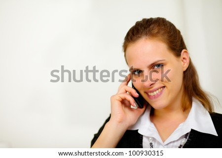 Close up portrait of a young beautiful smiling businesswoman on cellphone and looking to you - stock photo