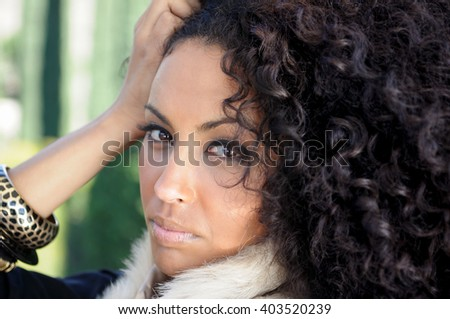 Close-up portrait of a young black woman, afro hairstyle, in urban background - stock photo