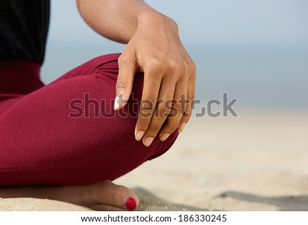 Close up portrait of a young black woman in lotus position with yoga hands at the beach  - stock photo