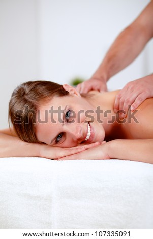 Close-up portrait of a young blonde girl relaxing at a spa while receiving a massage at spa resort with copyspace