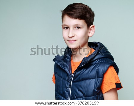 Close-up portrait of a young boy in an orange shirt and a dark blue vest, on a light blue background - stock photo