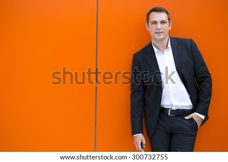 Close up portrait of a young business man in a dark suit and white shirt, against the backdrop of an orange wall - stock photo