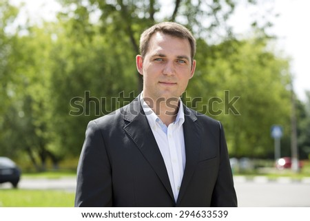 Close-up portrait of a young business man in a dark suit and white shirt on the background of summer city - stock photo