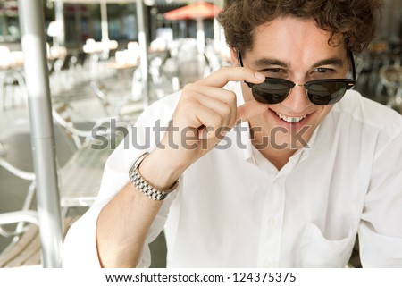 Close up portrait of a young businessman holding his shades to look at the camera smiling, while sitting at a coffee shop terrace, outdoors. - stock photo