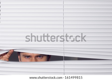 Close up portrait of a young businessman peeking through blinds - stock photo